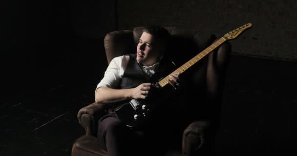 Kytarista sedí na křesle a hrát sólo na kytaru