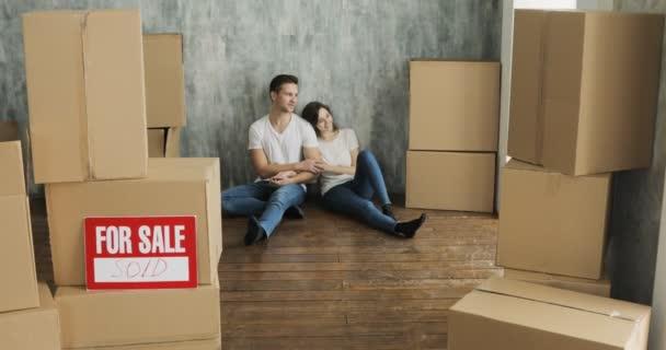 Junges Paar lacht nach dem Auspacken von Kartons beim Umzug