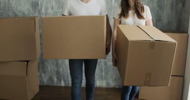 Paar trägt am Umzugstag Kisten in neues Zuhause oder neue Wohnung