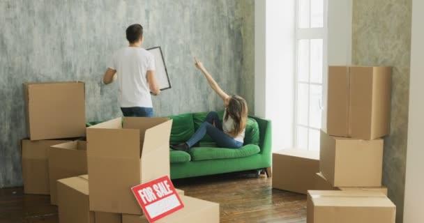 junges Paar wählt Punkt für Bild an der Wand zu Hause