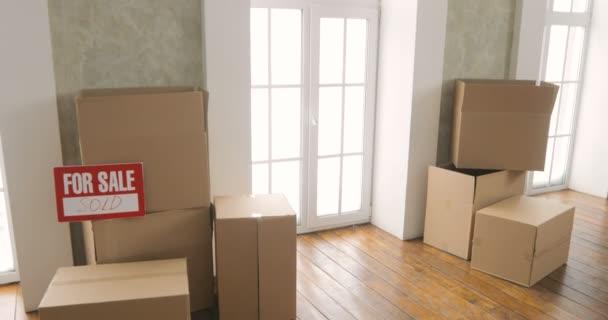 Neue Hausbesitzer beim Auspacken von Kartons. Bewegender Tag. Große Pappkartons im neuen Zuhause