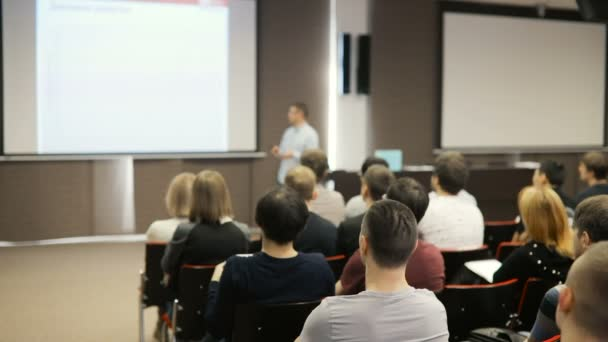 die Leute an einer Konferenz oder Präsentation, Workshop, Meisterklasse Fotografie. Dozent erzählt und Präsentation auf projektive Bildschirm zeigt. Ansicht von hinten