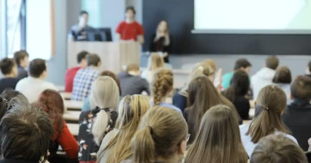 Skupina vysokoškolských studentů sedí ve svých křeslech v hledišti a poslouchal, jak jejich učitel pořádá přednášku