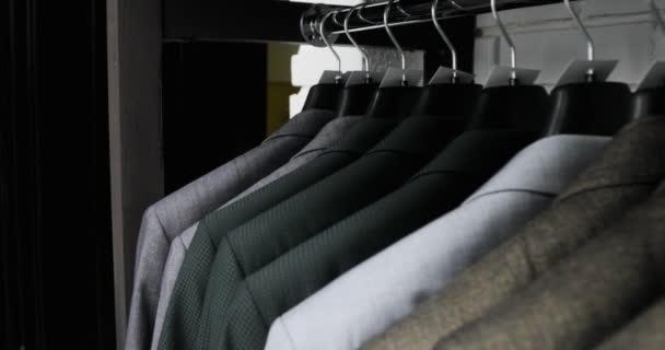 Pánská oblek v obchodě krejčích. Pánské ruce vybrat bundu v jejich šatníku. Muž volba