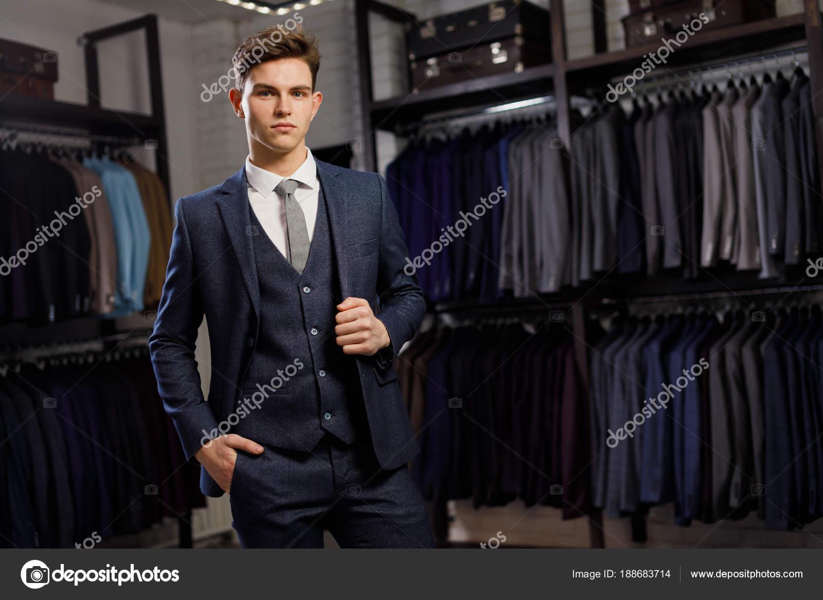 fae7a18003 Eladás, vásárlás, divat, stílus és az emberek koncepció - elegáns  fiatalember választotta és megpróbálja kabát mall vagy ruházati üzlet —  Fotó szerzőtől ...