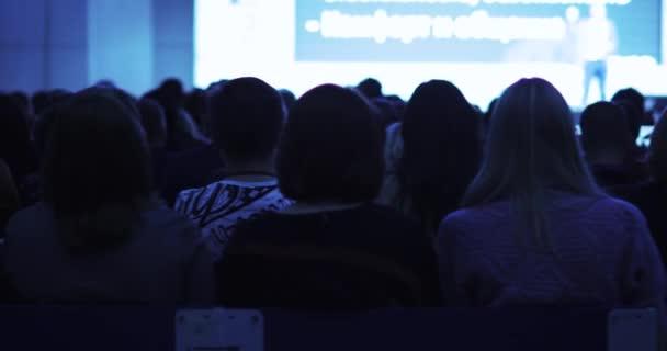 Zuschauer sehen Präsentation auf Leinwand und lauschen Redner auf der Bühne.