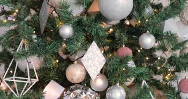 Rotating around Christmas tree decorated with silver balls and garlands.