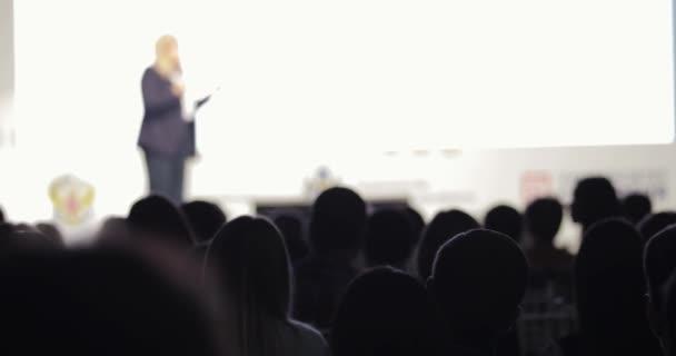 Üzletasszony a színpadon beszélő mikrofon ans bemutató a képernyőn.
