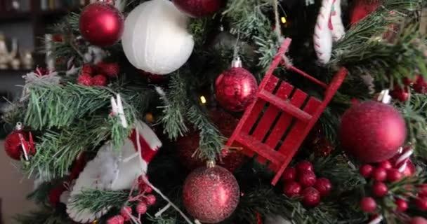 Forgó karácsonyfa vörös golyókkal, bogyókkal, ágakon koszorúkkal díszítve.