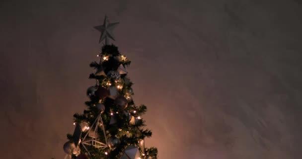 Karácsonyfa fényes koszorúval, díszített ezüst csillag a tetején és labdák.