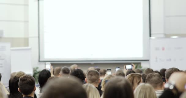 Zuschauer im großen Publikum fotografieren Bildschirm mit Präsentation, Rückseite.