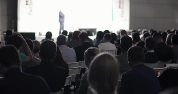 People listening businesswoman talking on stage and showing presentation.