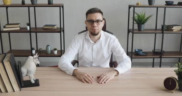 Young man office worker in glasses sitting at table and looking at camera.