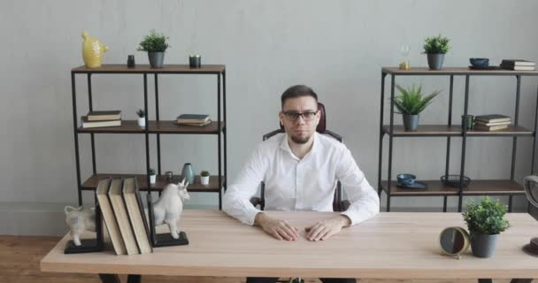 Serious young man office worker in glasses sitting at table looking at camera.