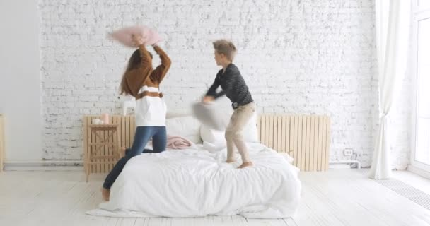 Šťastná rodina maminka a syn mají legrační polštář boj na posteli v jeslích doma.