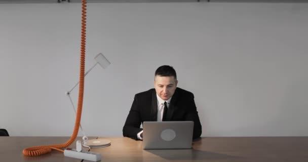 Ältere Mann Büroangestellte im Anzug arbeiten auf Laptop sitzen am Tisch, Vorderansicht.