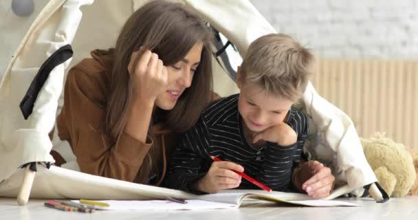 Portrét rodiny maminka a syn kreslení tužky v albu ležící v tipi.