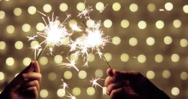 Ruce páru držící hořící jiskru na zlatém pozadí na Štědrý večer.