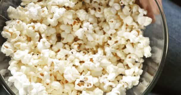Detailní ženské ruce přičemž popcorn z průhledné misky, horní pohled.