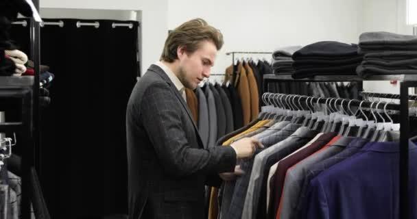 Mladý podnikatel je nakupování vybrat kancelářský oblek v obchodě s oblečením, boční pohled.