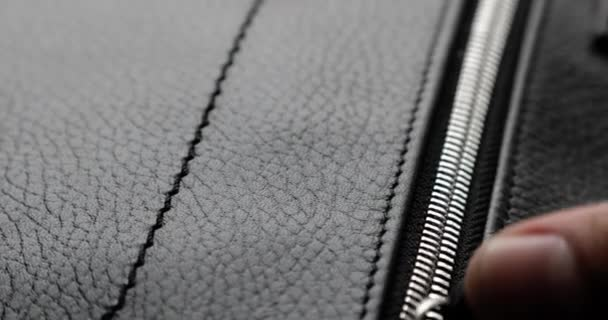 Testing metal zipper zips and unzips it on leather bag, mans hand closeup.