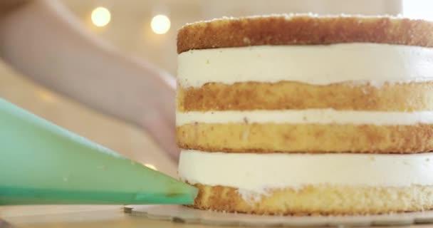 Cukrárna je nalévání krém na bocích dortu pomocí tašky, detailní záběr.