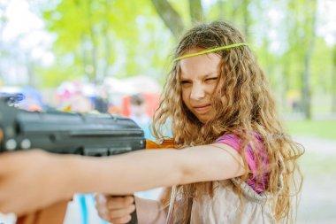 Little beautiful girl with Kalashnikov assault rifle at shooting range in city park in summer. stock vector
