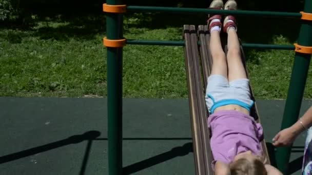 kleines Mädchen treibt Sport im Simulator, um den Bauch zu stärken.