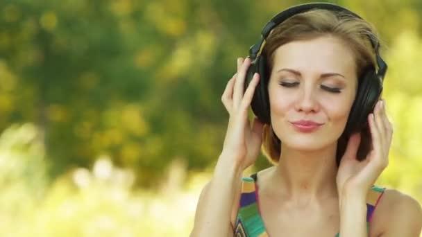 Fiatal gyönyörű nő, hallgató-hoz zene a háttérben a zöld nyári Városliget fejhallgató.