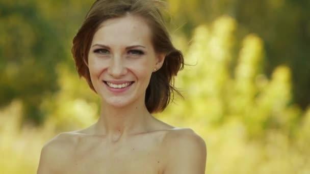 Mladá krásná žena s odhalenými rameny pozadí zelené letní městský park.