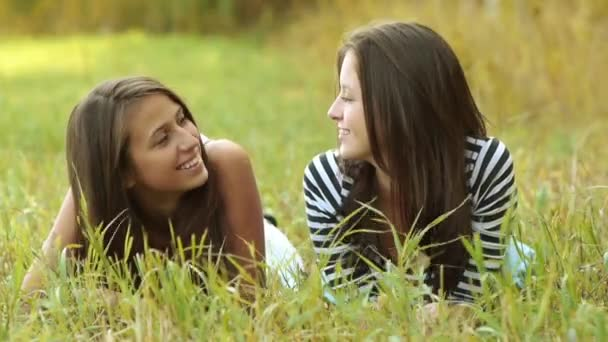 Two cheerful beautiful girls teenagers lie on grass and talking.