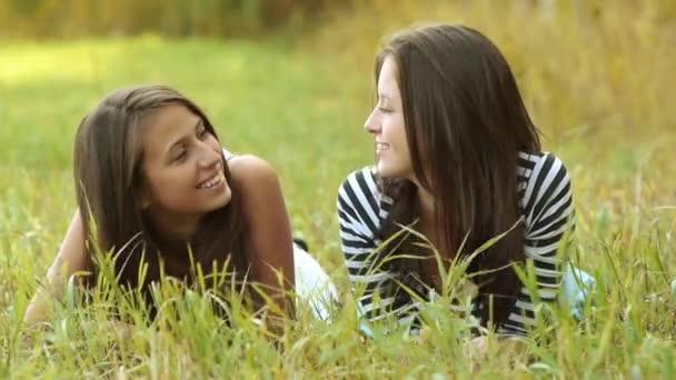 Due adolescenti allegro belle ragazze si trovano sullerba e ne