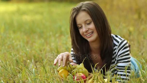 Fiatal gyönyörű nő fekszik, a zöld fű, és érett szőlőt enni.