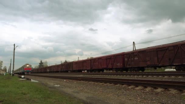 Příměstská osobní vlak jezdí letní krajinou v pozadí.