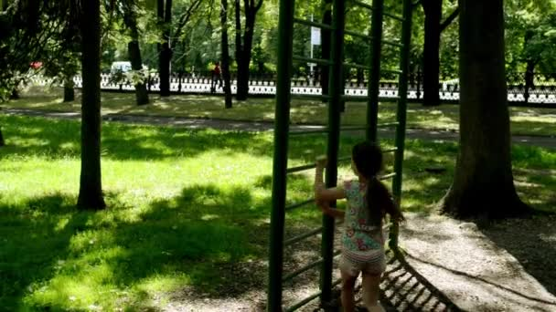 Malá krásná dívka se zabývá sportovní na vodorovných pruhů v létě městský park.