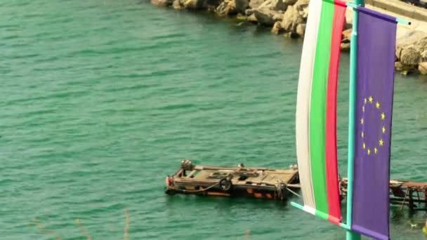 Flags of Bulgaria and European Union against backdrop of Black Sea coast.
