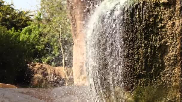 Vodopád, padající ze skály pozadí velkých Baobab.