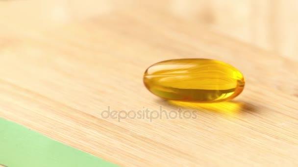 Kapsel mit Fischöl liegt auf Holztisch und dreht sich