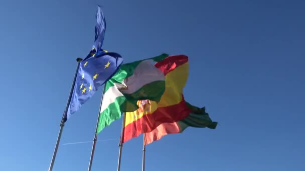 Flags of European Union, Spain, Andalusia and Granada flutter against blue sky.