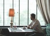 Mladý muž s šálkem kávy u okna