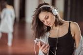 Young dancer with headphones on training in dance studio