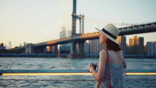 Atraktivní dívka s retro kamerou na Manhattanském mostě při západu slunce