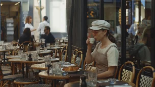Mladá dívka pije kávu v kavárně ráno