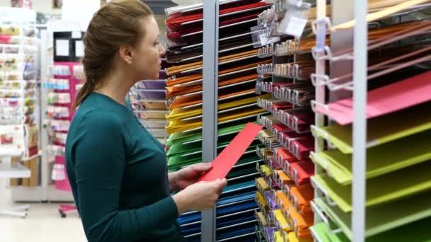 žena si koupí barevný papír v obchodě. 4k Uhd