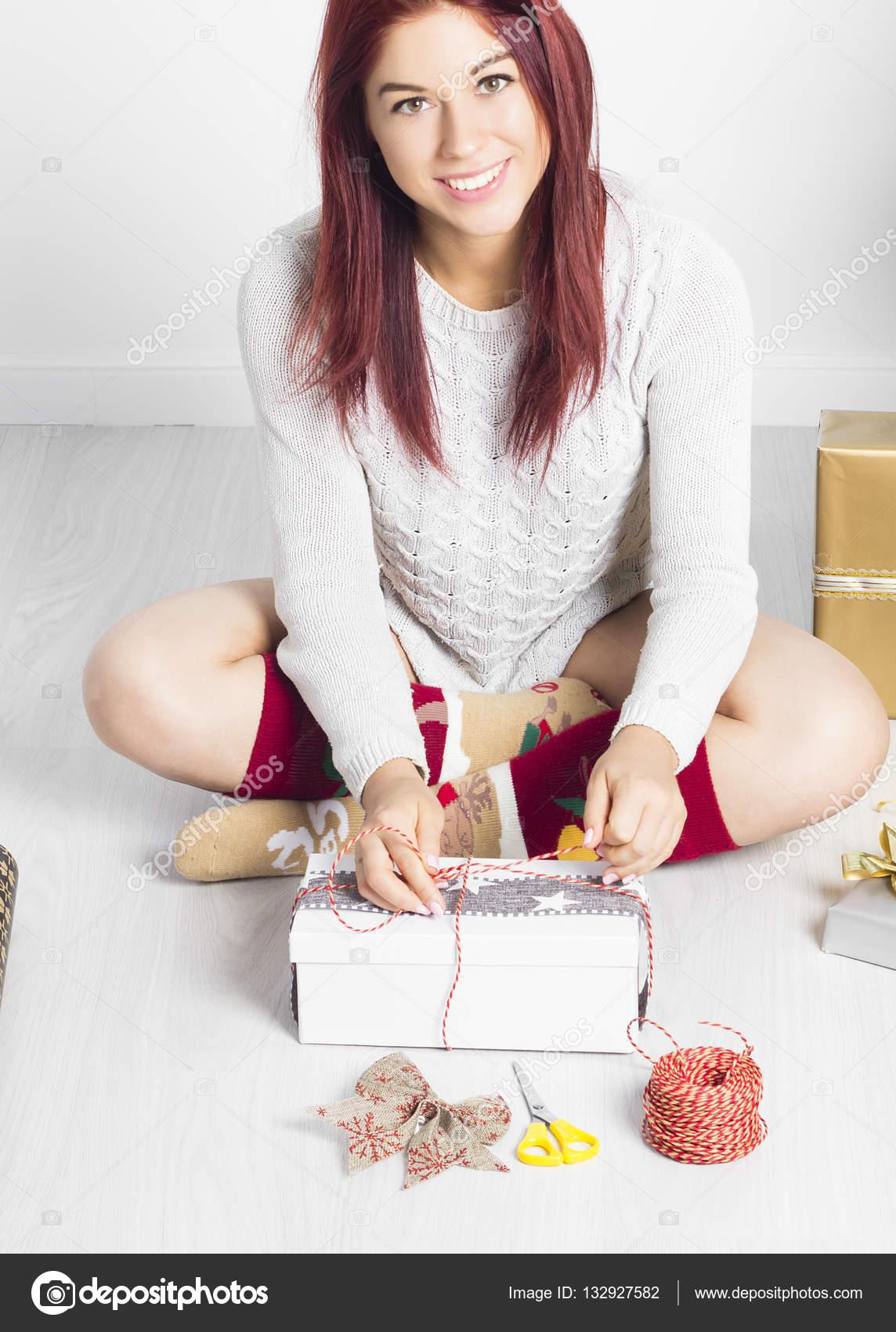 Glückliche Frau binden eine Schleife auf ein Weihnachtsgeschenk ...