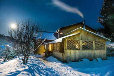 Wooden house in snow at winter night