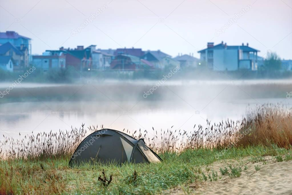 Green tent near river with morning mist