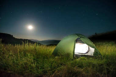 Green tent in mountains