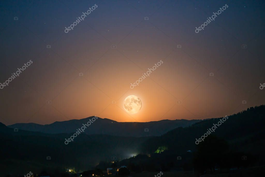 Moon rising on night sky