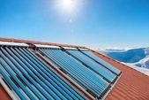 Fotografie Vakuum-Kollektoren - solare Warmwasserbereitung Rohre auf dem Dach des Hauses mit Sonne und Schnee Berge